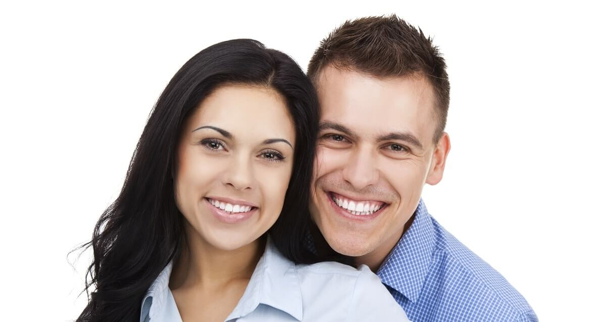 Young couple smiling into the camera.
