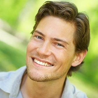 A man smiles to show how gum contouring can correct a gummy smile