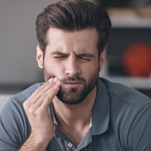 Man holding his cheek because of toothache pain to show that Dr. Graber is here for you if you have a dental emergency