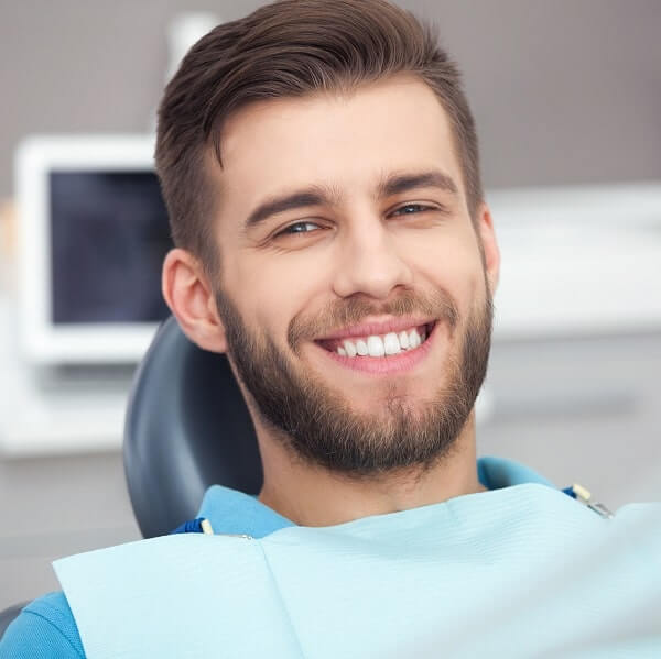 Smiling man in dental chair.