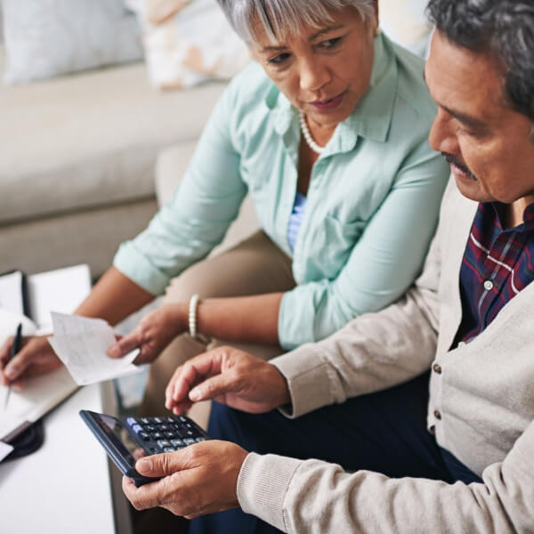 Older man and woman using calculator to balance budget to show that Dr. Graber accepts most dental insurance and provides financing options.