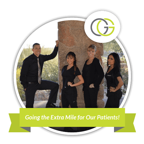 Dr Gregory Graber, your North Scottsdale dentist, and his dental team dressed in black and standing against a stone wall - with the text