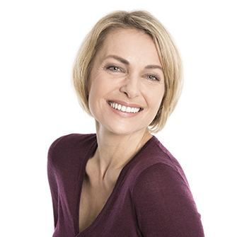 A smiling woman shows how dental implants restore your smile.