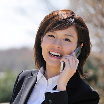 A businesswoman on the phone smiles to show off how porcelain veneers can enhance your smile